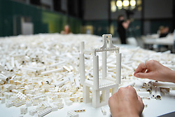 "© Licensed to London News Pictures. 26/07/2019. LONDON, UK.  A visitor works with Lego at the preview of ""The cubic structural evolution project"", 2004, by Olafur Eliasson at Tate Modern.  Exhibited for the first time in the UK, the artwork comprises one tonne of white Lego bricks inspiring visitors to create their own architectural vision for a future city and is on display until 18 August 2019.  The work coincides with the artist's new retrospective exhibition ""In real life"" at Tate Modern on display to 5 January 2020.  Photo credit: Stephen Chung/LNP"