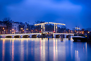 Here captured in the pre-dawn light, the Skinny Bridge is a popular Amsterdam landmark.