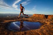 A trail runner taking a morning run along the canyon rim.<br /> Canyonlands National Park, Utah.