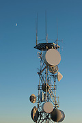 A microwave tower reaches towards the evening sky with the moon in the distance.
