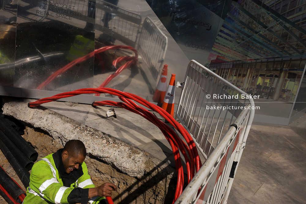UK Power Networks laying high-voltage cable in central London with reflective corporate backdrop behind.