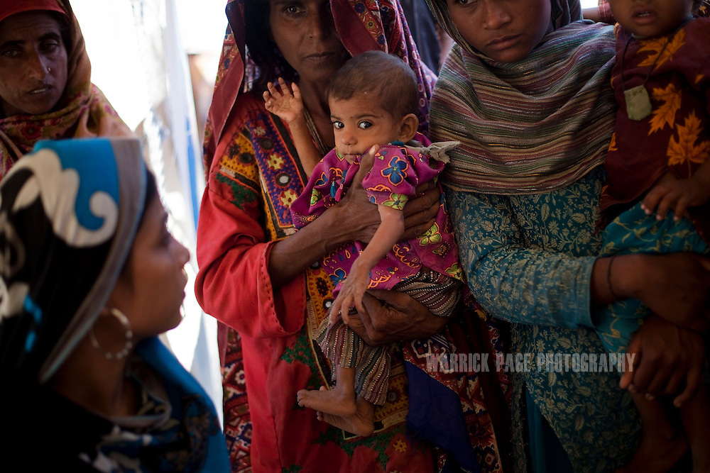 Banno, 30, holds her baby Ameena, 8 months, while they wait for health workers to check for signs of malnutrition, on October 15, 2011, in Pangrio, Pakistan. Banno has been suffering from TB for the last 12 months, while Ameena became malnourished 1 months before the floods began and became progressively worse after they were forced to flee their home. Extreme poverty, poor diet and health, exposure to disease, and inadequate sanitation and hygiene annually produce alarming levels of malnutrition amongst children, but the floods of 2010 and 2011 have increasingly endangered an already vulnerable population. Child malnutrition has breached emergency levels in Pakistan - particularly Sindh province - after monsoon floods devastated the country's poorest region for a second year. Malnourishment It is the single biggest contributor to under-five mortality, increasing the risk of infections and slowing recovery from illness. It stuns both mental and physical growth and their future capacity, sapping the next generation's ability to meet the demands of a country already facing an unstable future. According to UN reports, hundreds of thousands of children in Pakistan suffer from severe-acute-malnutrition, with 15.1% of children experiencing acute malnourishment. The Economist recently reported that 44% of children in Pakistan suffer from varying degrees of malnutrition. (Photo by Warrick Page)