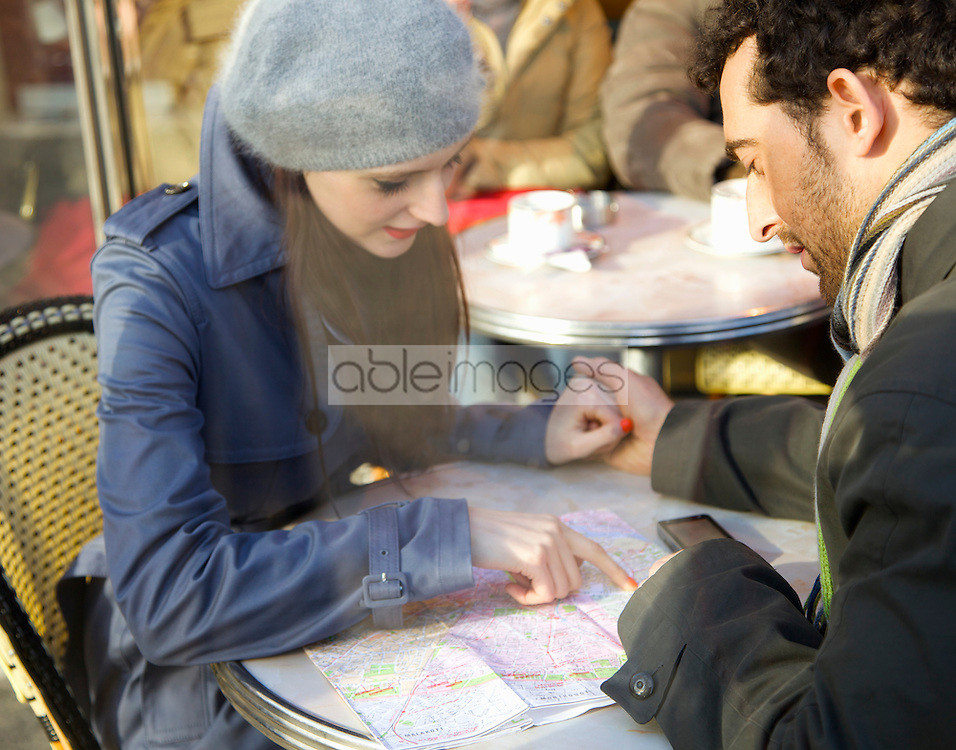 Young couple at cafe looking over a map