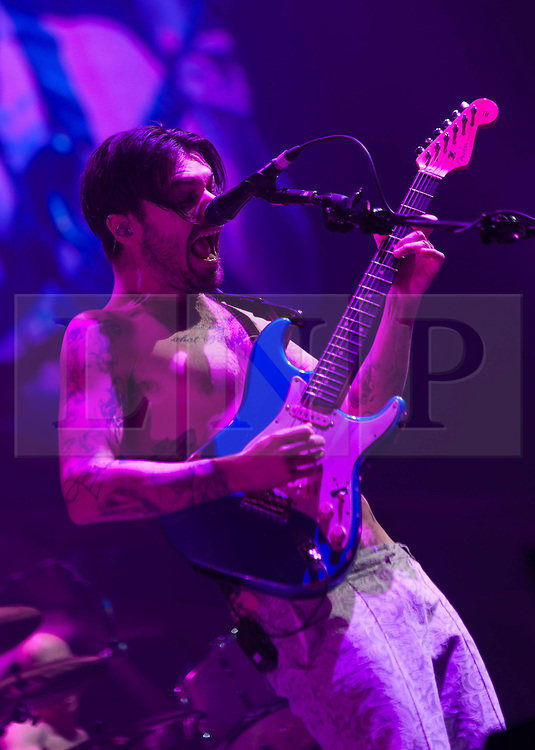 """© Licensed to London News Pictures. 03/04/2013. London, UK.  Simon Neil of Biffy Clyro performing live at O2 Arena. Biffy Clyro are a Scottish rock band comprising Simon Neil (guitar, lead vocals), James Johnston (bass, vocals) and Ben Johnston (drums, vocals).   This year they released their sixth studio album, """"Opposites"""".   Photo credit : Richard Isaac/LNP"""