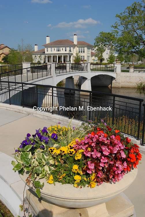 A vase full of assorted colorful flowers sit a an entrance to a walking bridge in front of mansions at the Baldwin Park neighborhood in Orlando, Florida.