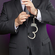 A businessman is using a key to unlock a pair of handcuffs. Image can be used metaphorically to represent business concepts about removing restrictions.