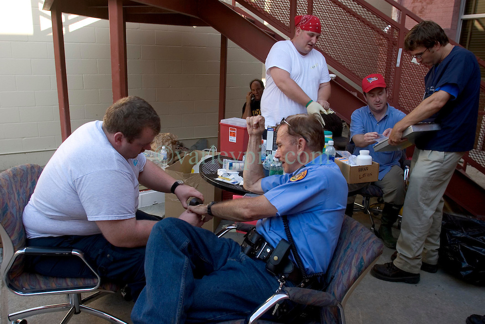 08 Sept 2005. New Orleans, Louisiana. Hurricane Katrina aftermath. <br /> Officer Frank Denton gets his hepatitis A and B and tetanus shots and health treatment from paramedics at a makeshift clinic at the 2nd precinct in uptown New Orleans.<br /> Photo; &copy;Charlie Varley/varleypix.com