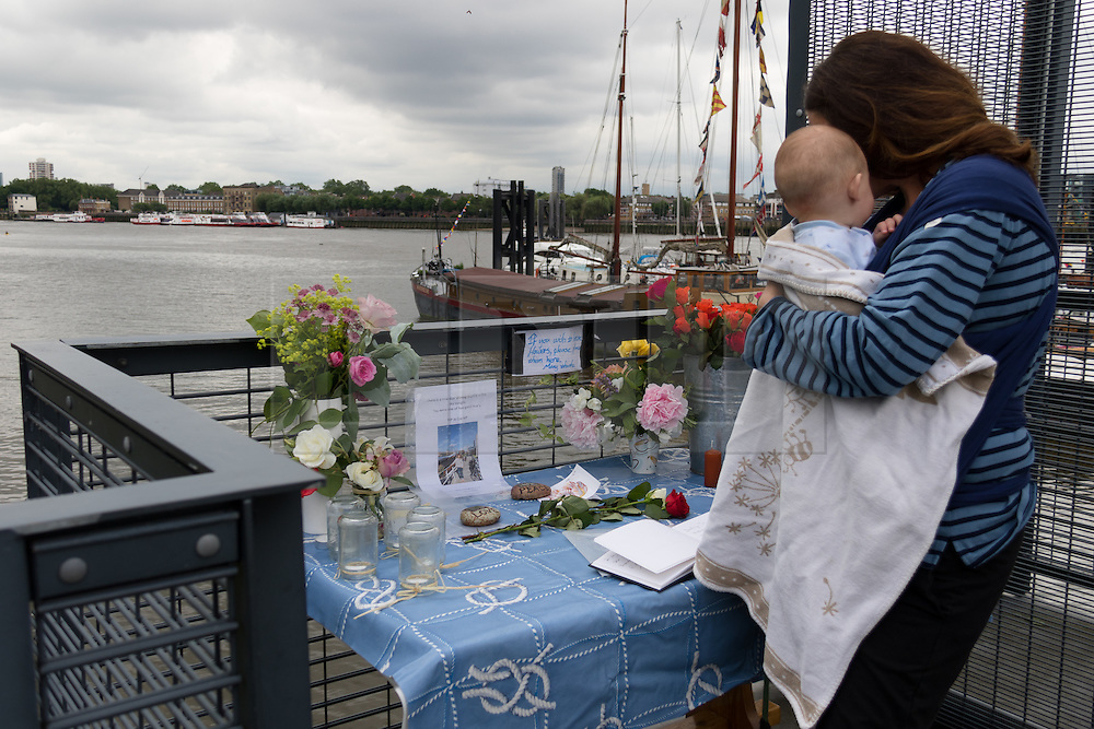 © Licensed to London News Pictures. 18/06/2016. LONDON, UK.  A friend of Jo Cox's with her baby look at the floral tributes and stones of love and peace with a condolence book on a tribute table outside Hermitage Moorings on the River Thames in Wapping, where the MP lived on a houseboat. The Labour MP for Batley and Spen was about to hold her weekly constituency surgery in Birstall Library on16 June 2016 when she was shot and stabbed in the street and later died. Friends and neighbours from the local community continue to visit Hermitage Moorings this morning to pay tribute to Jo Cox.  Photo credit: Vickie Flores/LNP