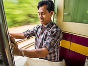 19 MARCH 2015 - AYUTTHAYA, AYUTTHAYA, THAILAND:  A man sits in the doorway of a third class train from Ayutthaya to Bangkok. The train line from Bangkok to Ayutthaya was the first rail built in Thailand and was opened in 1892. The State Railways of Thailand (SRT), established in 1890, operates 4,043 kilometers of meter gauge track that reaches most parts of Thailand. Much of the track and many of the trains are poorly maintained and trains frequently run late. Accidents and mishaps are also commonplace. Successive governments, including the current military government, have promised to upgrade rail services. The military government has signed contracts with China to upgrade rail lines and bring high speed rail to Thailand. Japan has also expressed an interest in working on the Thai train system. Third class train travel is very inexpensive. Many lines are free for Thai citizens and even lines that aren't free are only a few Baht. Many third class tickets are under the equivalent of a dollar. Third class cars are not air-conditioned.   PHOTO BY JACK KURTZ