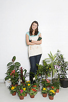 Portrait of woman surrounded by various potted plants