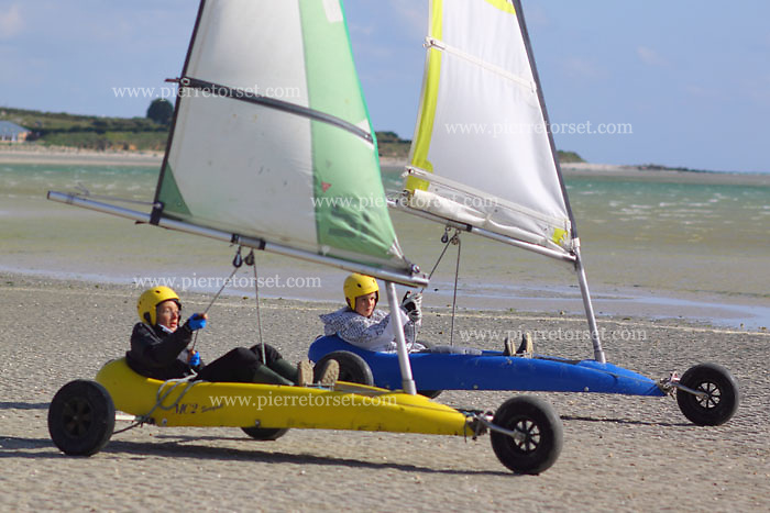 Land sailing is also known as sand yachting or land yachting. It is the act of moving across land in a wheeled vehicle powered by wind through the use of a sail. The term comes from analogy with (water) sailing. Historically, land sailing was used as a mode of transportation or recreation. Since the 50s it has evolved primarily into a racing sport..Vehicles used in sailing are known as sail wagons, sand yachts or land yachts. They are typically three-wheeled vehicles that function much like a sailboat, except that they are operated from a sitting or lying position and steered by pedals or hand levers. Land sailing works best in windy, flat areas, and races often take place on beaches, air fields, and dry lake beds in desert regions. Modern land sailors, generally known as 'pilots', can go three to four times faster than the wind speed, because of Bernoulli's principle.[citation needed] A gust of wind is considered more beneficial in a land sailing race than a favorable windshift. Picture was taken in Brittany, France, in some watersports centers, where windy conditions are adequated.