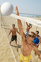 Small group of young men playing volleyball on beach outstanding the point