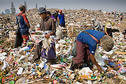 "25 FEBRUARY 2008 -- MAE SOT, TAK, THAILAND: Burmese migrant workers go through garbage in the dump in Mae Sot, Thailand. Hundreds of Burmese migrants eke out a living in the dump going through the garbage to sell what they find. There are millions of Burmese migrant workers and refugees living in Thailand. Many live in refugee camps along the Thai-Burma (Myanmar) border, but most live in Thailand as illegal immigrants. They don't have papers and can not live, work or travel in Thailand but they do so ""under the radar"" by either avoiding Thai officials or paying bribes to stay in the country. Most have fled political persecution in Burma but many are simply in search of a better life and greater economic opportunity.  Photo by Jack Kurtz"