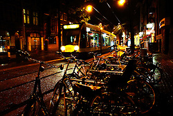 A tram passes by rows of bicycles.