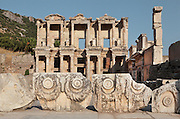 Library of Celsus, built 110-135 AD under Consul Julius Celsus Polemaenus, governor of the province of Asia, Ephesus, Izmir, Turkey. Celsus paid for the construction with his own personal wealth, and is buried in a sarcophagus beneath it. The library held nearly 12,000 scrolls in cupboards in niches in the double walls, which protected the documents from temperature and humidity. In the foreground are carved stone blocks with bull's heads and garlands. Ephesus was an ancient Greek city founded in the 10th century BC, and later a major Roman city, on the Ionian coast near present day Selcuk. Picture by Manuel Cohen