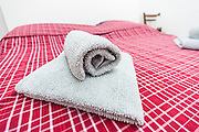 Rolled towel on bed welcoming new guests