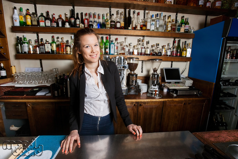 Portrait of happy female cashier at counter in restaurant