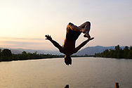 Khmer man jumping in the Kampong Bay River in Kampot, Cambodia.<br />