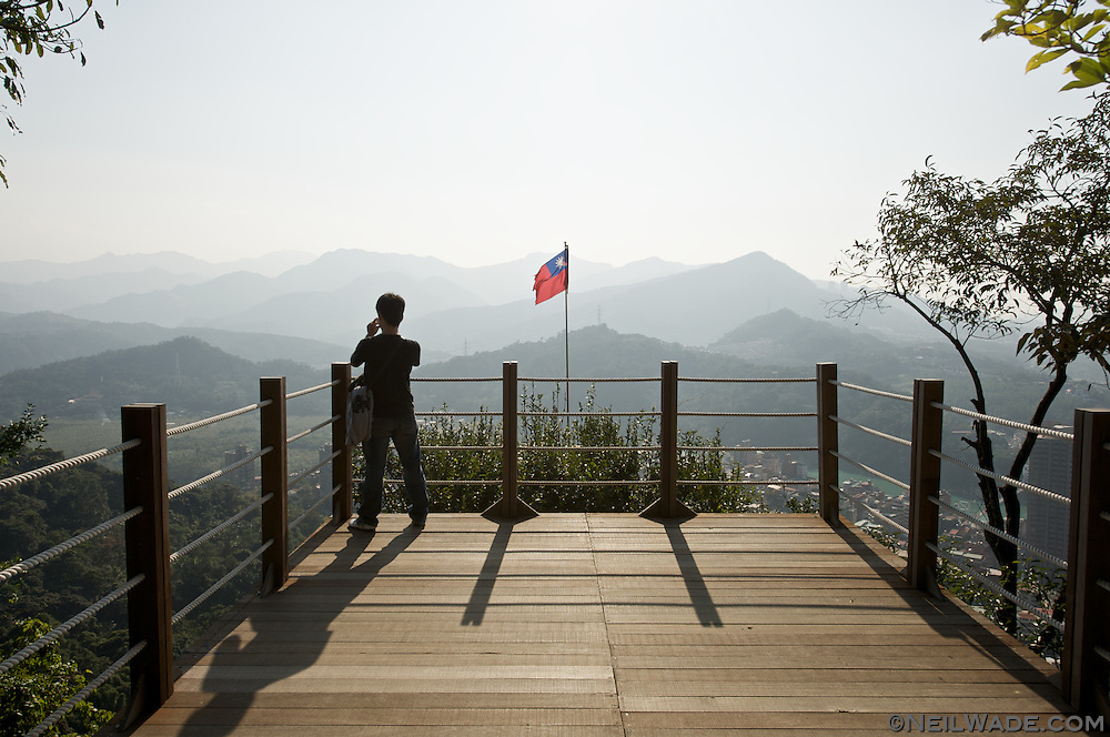 A hiker has a look around the mountains on a observation deck in Taipei, Taiwan.
