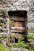 Ticino, Southern Switzerland. The remains of an ancient wooden door set in a stone building in Verdasio.