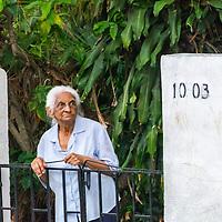 Una señora del barrio Pedregal se asoma a la puerta de su casa, momentos antes de la quema de Judas en el domingo de Pascua. A lady from Pedregal neighborhood peers out the door of her house just before Judas burns on Easter Sunday. Caracas, Venezuela