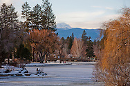 A downtown park with a frozed lake in winter with sunshine and a view of the mountain and foothills in the disance
