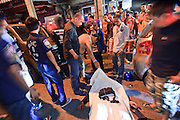 "02 OCTOBER 2009 -- BANGKOK, THAILAND: People pull up a sheet to look at a man who died in a motorcycle accident in Bangkok. The 1,000 plus volunteers of the Poh Teck Tung Foundation are really Bangkok's first responders. Famous because they pick up the dead bodies after murders, traffic accidents, suicides and other unplanned, often violent deaths, they really do much more. Their medics respond to medical emergencies, from minor bumps and scrapes to major trauma. Their technicians respond to building collapses and traffic accidents with heavy equipment and the ""Jaws of Life"" and their divers respond to accidents in the rivers and khlongs of Bangkok. The organization was founded by Chinese immigrants in Bangkok in 1909. Their efforts include a hospital, college tuition for the poor and tsunami relief.   PHOTO BY JACK KURTZ"