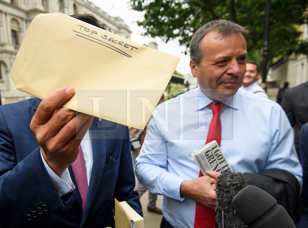 """© Licensed to London News Pictures. 12/06/2018. London, UK.   Leave.EU founder ARRON BANKS and Leave.EU campaigner ANDY WIGMORE hold a """"TOP SECRET"""" envelope as they arrive at Portcullis House in London where they are due to give evidence to a Commons Digital, Culture, Media and Sport Committee about fake news. The pair have been accused of collusion with Russian officials around the time of the Brexit referendum. Photo credit: Ben Cawthra/LNP"""
