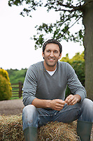 Man sitting on hay bale in countryside portrait