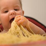 A ten month old baby girl eating pasta. Photo Tim Clayton