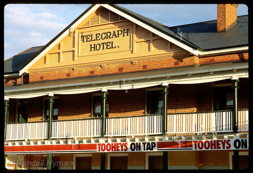 Balcony of Telegraph Hotel soaks in late afternoon sun, sporting Toohey beer advertisement; NSW. Australia