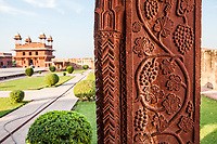 A courtyard in the Fatehpur Sikri complex with detail of stone carved pillar in foreground.
