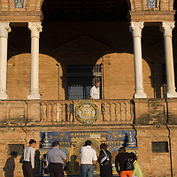 People looking at the tiled alcoves of the 1929 Exposition Building, Plaza de España, Sevilla, Andalucia, Spain.