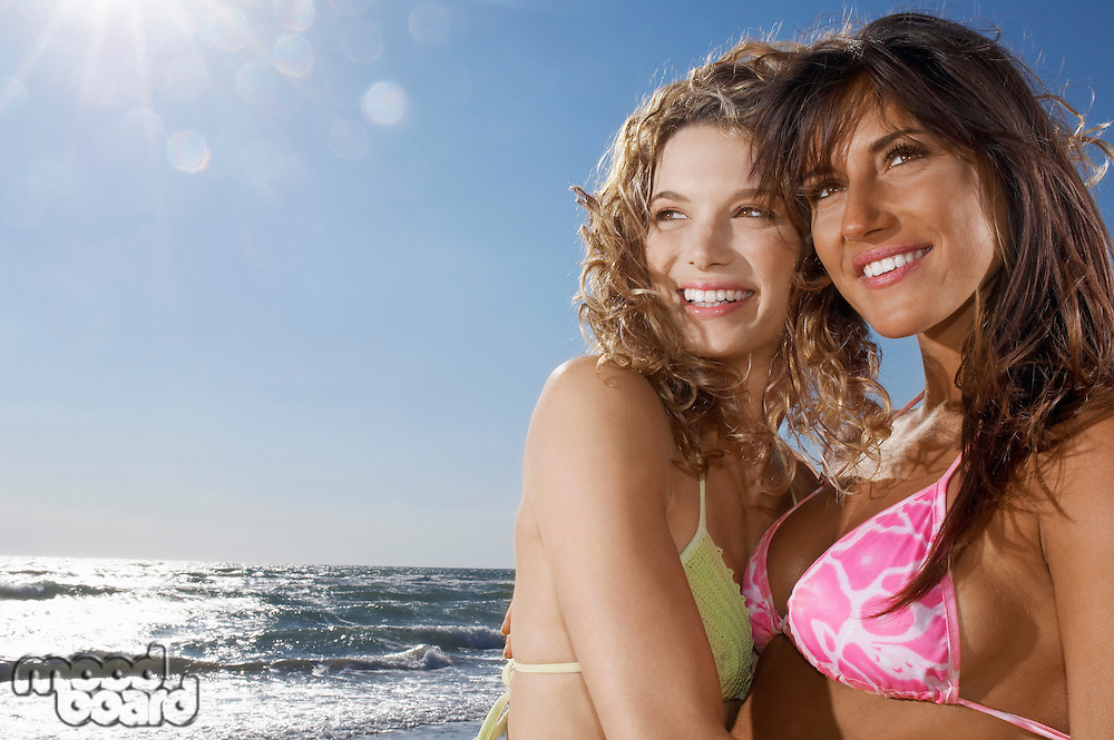 Two young women hugging on beach in bikinis close up