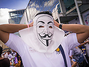 "09 JUNE 2013 - BANGKOK, THAILAND:   A Thai White Mask ties on his Guy Fawkes mask at Central World in Bangkok. The White Mask protesters wear the Guy Fawkes mask popularized by the movie ""V for Vendetta"" and the protest groups Anonymous and Occupy. Several hundred members of the White Mask movement gathered on the plaza in front of Central World, a large shopping complex at the Ratchaprasong Intersection in Bangkok, to protest against the government of Thai Prime Minister Yingluck Shinawatra. They say that her government is corrupt and is a ""puppet"" of ousted (and exiled) former PM Thaksin Shinawatra. Thaksin is Yingluck's brother. She was elected in 2011 when her brother endorsed her.    PHOTO BY JACK KURTZ"