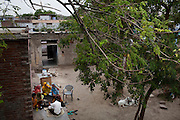 Nafeesa (center, in blue), 27, rolls bidis (indian cigarettes) with other village women as her 4 children aged 10, 7, 4, and 1 and a half years, play in her house compound in a slum in Tonk, Rajasthan, India, on 19th June 2012. Nafeesa's health deteriorated from bad birth spacing and over-working. While her husband works far from home, she rolls bidis to make an income and support the family. She single-handedly runs the household and this has taken a toll on her health and financial insufficiencies has affected her children's health. Photo by Suzanne Lee for Save The Children UK