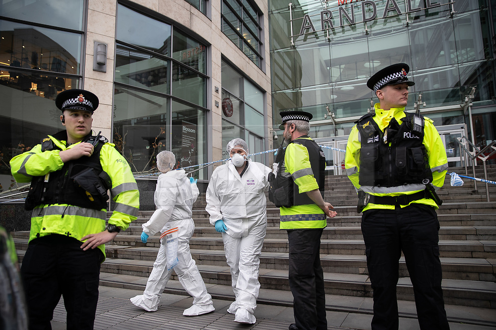 © Licensed to London News Pictures. 11/10/2019. Manchester, UK. Police and forensic scenes of crime examiners in front of the entrance to the Arndale Centre . Terrorism Police are investigating after four people were stabbed during a single attack at the Arndale Centre in Manchester City Centre . Photo credit: Joel Goodman/LNP