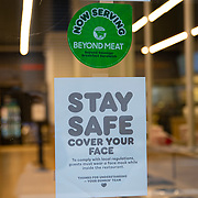 A sign in a Dunkin Donuts shop window reminds guests to wear a face mask due to the Coronavirus (Covid-19) outbreak in New York City, New York on Friday, May 8, 2020.  (Alex Menendez via AP)
