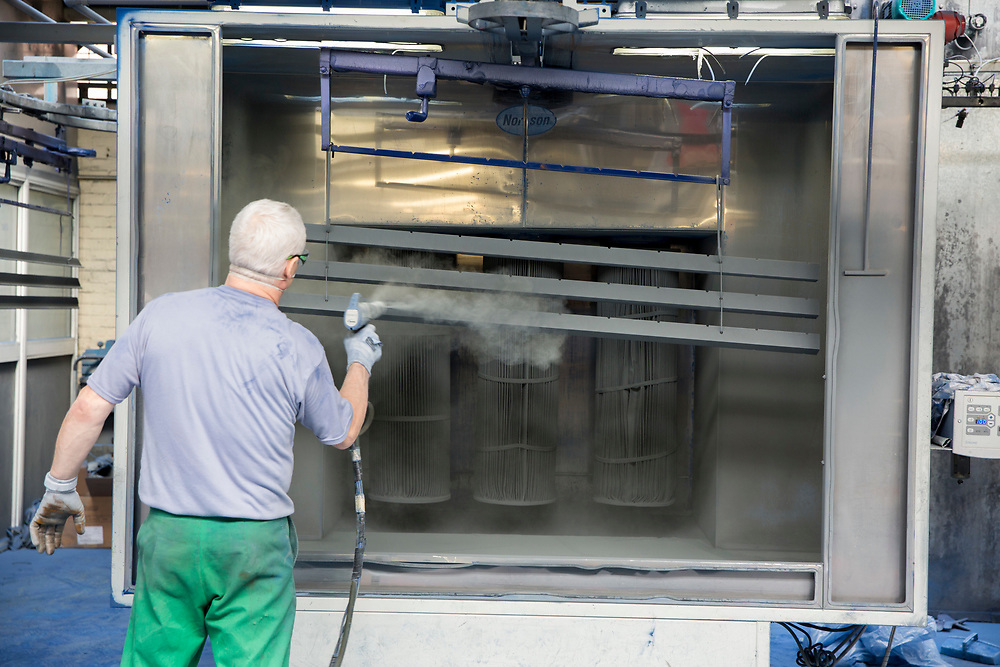 A prisoner powder coating metal bars in the steel industries workshop of HMP Coldingley. Surrey, United Kingdom. HMP Coldingley is a category C training prison, focussed on the resettlement of prisoners. All inmates must work a full working week, within the prison grounds.