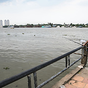 A man fishes from a small pier on the banks of the Saigon River in Ho Chi Minh City, Vietnam.