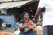 Joy buying some fresh tomatoes from the market.<br /> <br /> Joy Kalu runs Goodness Catering Services, which is a restaurant and events catering business.<br /> <br /> Joy began her catering business in 1999. She started off just making 10 or 15 soups to sell each day but soon the business grew and she started diversifying the range of food she sold. After three years she moved into her premises at the local market and her business developed into catering for events such as weddings and funerals.<br /> <br /> The main thing Joy learnt on the Youth for Technology training was the importance of capital investment.