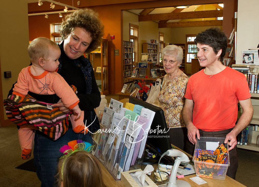 Wendy Ouellers holds her 5 month old granddaughter Zoe Criscone as she receives her very first Halloween treat from Dorothy Kereage and Joanne Buckner at Gilford Library's annual Halloween Parade and Party on Wednesday morning.  (Karen Bobotas/for the Laconia Daily Sun)
