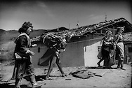 Young Tibetan women perform roof repairsto their wood and mud-plaster home, wearing traditional clothing,  during the dry winter season in preparations for the wet summer season in 1997  Gyalthang Teng (now known as Shangri-La in Chinese).  Kham, Tibet (Yunnan, China)