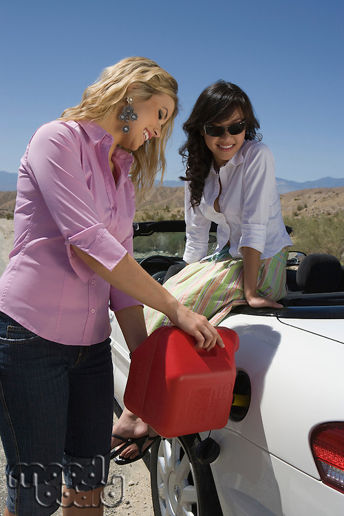 Two young women refuelling car on road