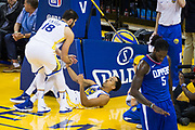 Golden State Warriors guard Shaun Livingston (34) is helped up by Golden State Warriors forward Omri Casspi (18) after being fouled by LA Clippers forward Montrezl Harrell (5) at Oracle Arena in Oakland, Calif., on January 10, 2018. (Stan Olszewski/Special to S.F. Examiner)