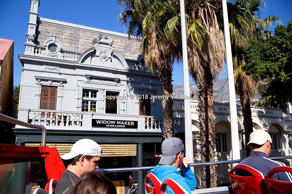 A Tourist bus passes along an old fashion barbershop along Long Street in Cape Town.<br />