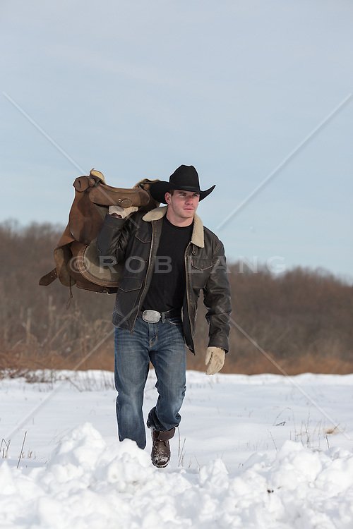 cowboy walking through snow while carrying a saddle over his shoulder