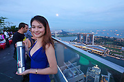 Singapore. Marina Bay Sands Hotel and Central Business District seen from Altitude restaurant and bar at the 61st and 62nd floor of One Raffles Place.<br /> Vodka promotion girl.