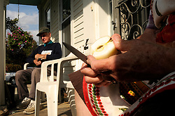 Carl Adams sits on the porch after planting 30 of a planned 200 bulbs for spring flowers as Pat Adams cuts up MacIntosh apples from a tree in her Lebanon yard to freeze for winter pies Friday, September 30, 2011. <br /> Valley News - James M. Patterson<br /> jpatterson@vnews.com<br /> photo@vnews.com