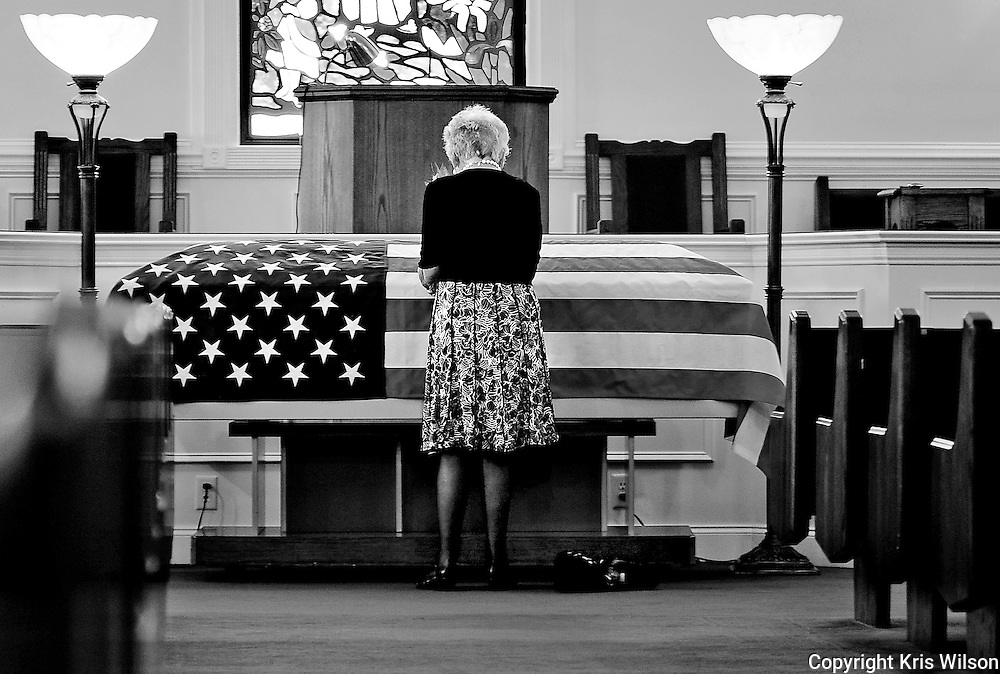 Ann Head Witkowski spends time alone visiting the flag-draped coffin containing the remains of her husband, former Korean War P.O.W. Master Sgt. Roy E. Head. These few minutes were the first in nearly 60 years she'd had to be close to her husband. Photo by Kris Wilson.